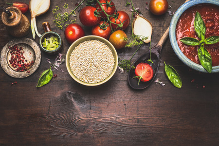 Quinoa in bowl with wooden spoon and vegetables and seasoning cooking ingredients on rustic background, top view