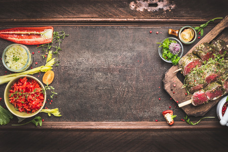 flavoring: Meat skewers with vegetables and fresh flavoring, preparation for grill or BBQ on dark vintage background, top view, banner