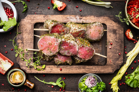 meat grill: Meat skewers with green herbs crust for grill or cooking, preparation on dark rustic wooden background, top view Stock Photo