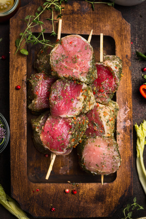 meat skewers: Raw meat skewers with fresh seasoning crust in rustic wooden plate, top view, close up