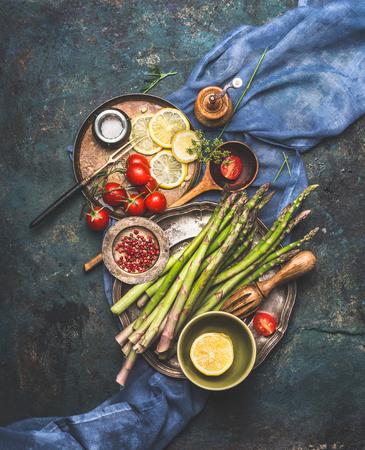 Vegetables cooking ingredients: green asparagus,tomatoes, lemon and flavoring on dark rustic background , top view