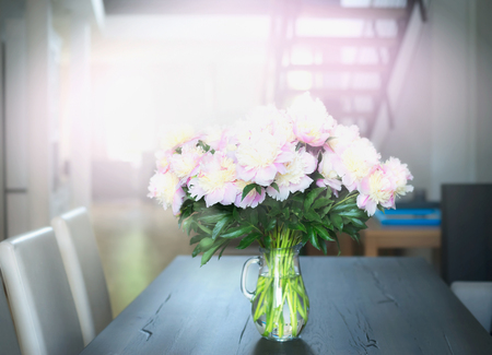 interior decor: Bouquet of light pink pastel peonies on a dining table in the living room. Home decoration