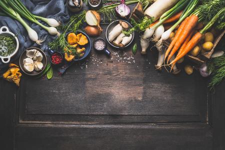 Bio-Ernte Gemüse aus dem Garten und Waldpilzen. Vegetarische Zutaten für das Kochen auf dunklen rustikalen hölzernen Hintergrund, Ansicht von oben, Grenze