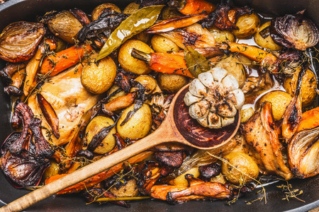hunters: Cooked rabbit stew with  forest mushrooms , roasted vegetables of season and rustic wooden spoon, top view, close up Stock Photo