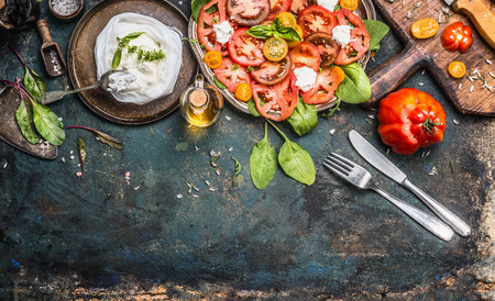 preparation: Tomatoes and mozzarella salad, preparation on dark aged rustic background, top view. Italian lunch with tomatoes and mozzarella, cutlery  and cooking ingredients. Italian food concept Stock Photo