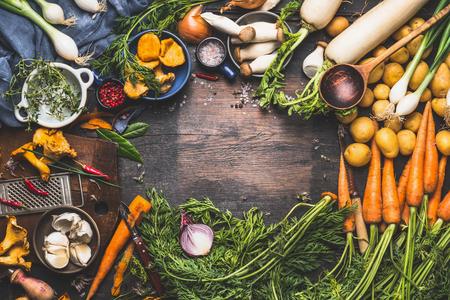 Groenten koken ingrediënten voor smakelijke vegetarische gerechten. Wortel, aardappel, ui, champignons, knoflook, tijm, peterselie op donkere rustieke houten achtergrond, frame