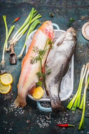 rainbow fish: Raw whole trout fish and Gold Rainbow trout on dish in dish with  ice cubes and fresh cooking ingredients on dark rustic background, top view. Healthy or diet food concept Stock Photo