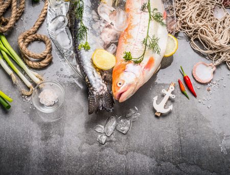 Fresh raw whole fish with ingredients for tasty and healthy cooking on concrete stone background with ice cubes, top view, border. Gold Rainbow trout cooking. Healthy or diet food concept