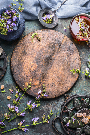 wild mint: Vertical tea background. Fresh healing herbs and flowers with glass cup and vintage tea setting on dark background, top view, frame. Healthy ,healing or detox drinks concept