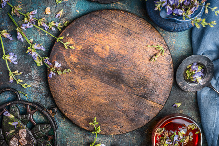 Herbal tea background with round wooden board, cup of tea and various flowers and healing herbs on dark background, top view, frame, horizontal. Healthy ,healing or detox drinks concept