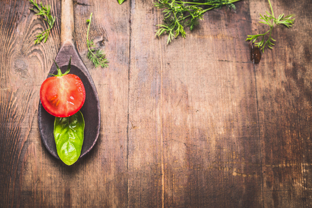 simple meal: Rustic food background for cooking or recipes with wooden spoon , basil leaf and tomato, top view. Simple, vegetarian or Mediterranean food concept.