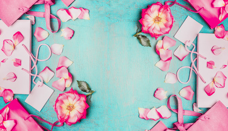 blue petals: Lovely pink flowers with petals and pink paper shopping bags on light blue background, top view, banner. Summer sale and shopping background