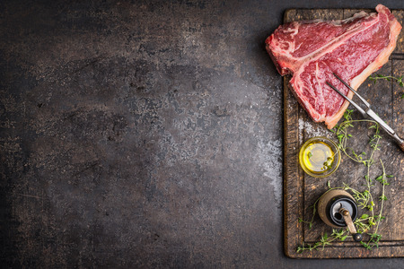 Raw T-bone Steak for grill or BBQ with meat fork and flavoring on aged cutting board and dark rustic metal background, top view, border Stock Photo