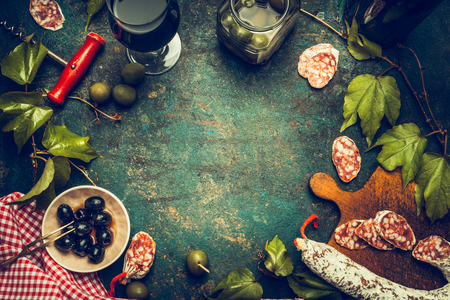 Dark italian food and antipasti background with wine,salami,olives and kitchen tools, top view, frame. Italian food background for menu or recipes . Stock Photo