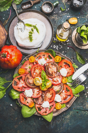 chees: Caprese tomatoes mozzarella salad in aged metal plate with homemade chees and ingredients on dark rustic background, top view