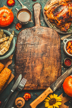 ロースト チキンやトルコ、カボチャ、トウモロコシ、野菜を収穫包丁、刃物周り暗い素朴な背景に高齢者の木製のまな板を楽しめます、フレームし