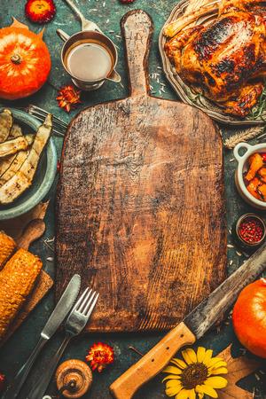 Geroosterde gehele kip of kalkoen, pompoenen, maïs en oogstgroenten met keukenmes en bestek geserveerd rond oud houten snijplank op donkere rustieke achtergrond, frame. Thanksgiving Day eten