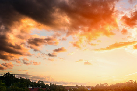 sky sun: Beautiful sunset sky with clouds and sun light above green trees and village Stock Photo