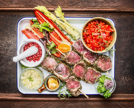 meat skewers: Raw marinated meat skewers with spices and vegetables for grill or roasting on dark wooden background, top view Stock Photo