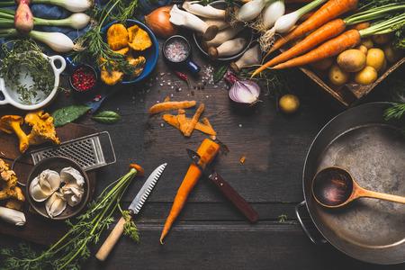 Koken met bos paddenstoelen en groenten ingrediënten en keukengereedschap, voorbereiding op donkere rustieke houten tafel, bovenaanzicht Stockfoto