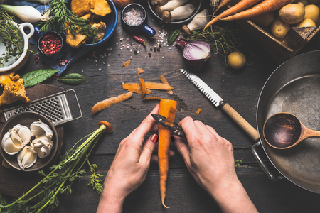 Female woman hands peeling carrots on dark wooden kitchen table with vegetables cooking ingredients, spoon and tools, top view Stock Photo