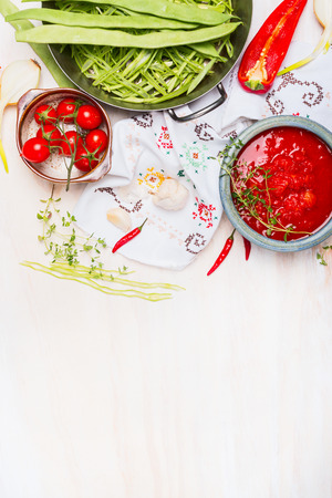 ejotes: Green beans with tomatoes sauce, cooking  preparation on light wooden background with traditionally embroidered cloth and ingredients, top view, place for text Foto de archivo