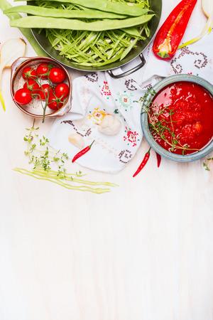 ejotes: Habas verdes con salsa de tomate, preparación de cocina sobre fondo de madera con paño tradicionalmente bordado e ingredientes, vista superior, lugar para el texto