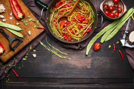 tomato sauce: Green beans with tomatoes sauce in cooking pot with ingredients on cutting board for vegetarian dish on dark rustic wooden background, top view