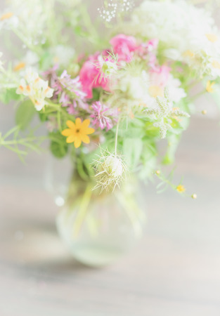 luz natural: Beautiful wild flowers bunch in glass vase on light background, soft focus, close up. Home   decoration and interior