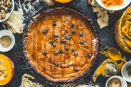 retro dark: Traditional pumpkin pie with seeds and ingredients on dark rustic background, top view, retro styled