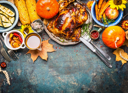 Festive  Thanksgiving Day food background with roasted whole turkey or chicken and sauce, harvest vegetables: corn, pumpkin,carrots with cutlery on dark rustic kitchen table, top view, border Stock Photo