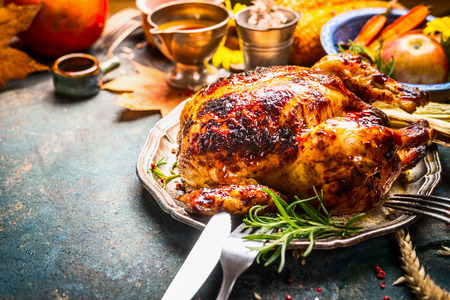 Roasted whole turkey or chicken on festive rustic table with festive autumn decoration for  Thanksgiving Day