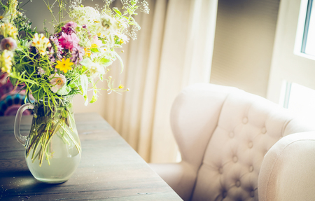floral decoration: Glass vase with  wild field flowers bunch on dinning table with chair at window. Floral home decoration Stock Photo