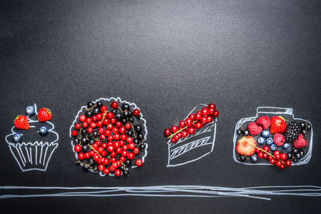 Various fresh summer berries and painted cupcake ,cake,tart, and jam jar on blackboard background. Berries food concept