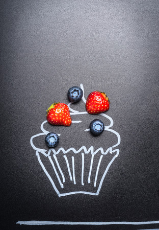 drawed: Fresh berries with painted cupcake on blackboard background.Berries food concept Stock Photo