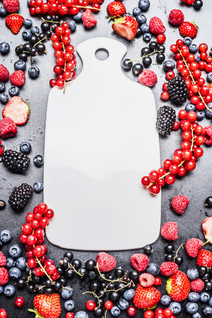 fame: White cutting board and fresh summer berries on dark background, top view, fame
