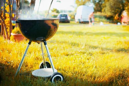 Grill met rook in de late zomer of herfst achtergrond van de natuur in een park of tuin met silhouetten van auto's en mensen