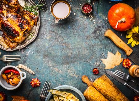 Gebratenes vollständiges Huhn oder Truthahn mit Soße und gegrilltem Gemüse Herbst: Mais, Kürbis, Paprika auf dunklem Hintergrund rustikalen, Ansicht von oben, Rahmen. Thanksgiving Day-Food-Konzept