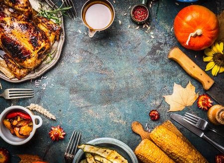 Helstekt kyckling eller kalkon med sås och grillade höst grönsaker: majs, pumpa, paprika på mörk lantlig bakgrund, ovanifrån, ram. Thanksgiving Day matkoncept