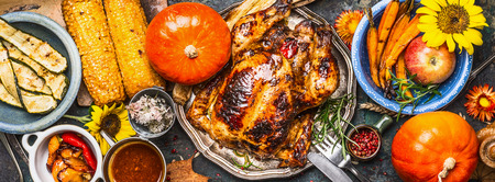Thanksgiving Day food. Various grilled vegetables ,roasted chicken or turkey and pumpkin with sunflowers decoration on dark background, top view, banner