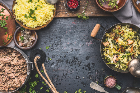 variety: Delicious dish with  stewed chopped cabbage and mushrooms, yellow rice and mincemeat on dark background , top view. Rustic food cooking