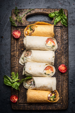 Variety of vegetarian tasty wraps on rustic cutting board on dark background, top view. Healthy lunch snack