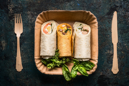paper plates: Vegetarian tortilla wraps in paper plate and wooden cutlery on dark background, top view, close up. Healthy lunch snack or street food concept