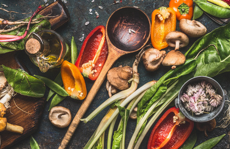 variety: Various fresh vegetables with wooden cooking spoon for healthy  eating and nutrition on dark rustic background, top view