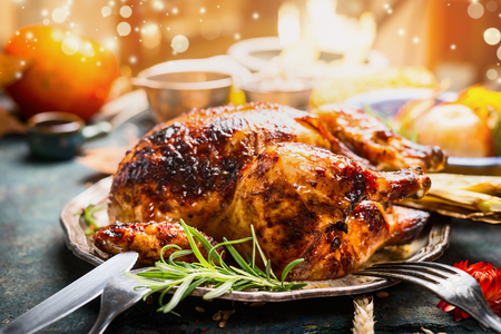 feestelijk: Thanksgiving day diner tabel instelling met Geheel gebraden kalkoen of kip op bord met bestek, feestelijke verlichting en decoratie, close-up Stockfoto
