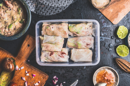 box: Preparation of Healthy Lunch box with summer rolls of tuna fish, avocado and ingredients, top view
