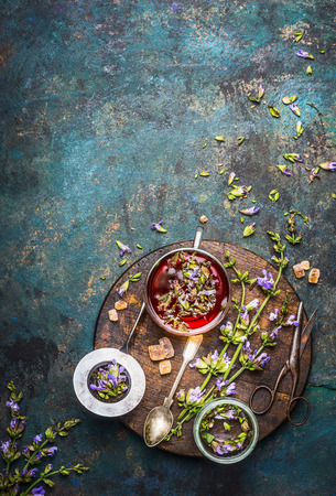 Herbal tea preparation with fresh healing herbs and flowers on dark rustic background, top view Imagens
