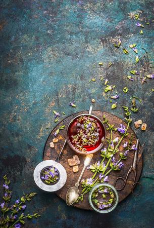 Kruiden thee bereiding met verse helende kruiden en bloemen op donkere rustieke achtergrond, bovenaanzicht