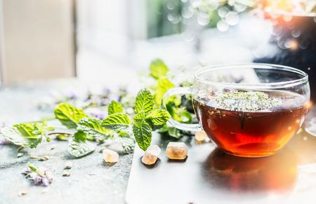 taza de té: Taza de té de hierbas en la ventana todavía, de cerca