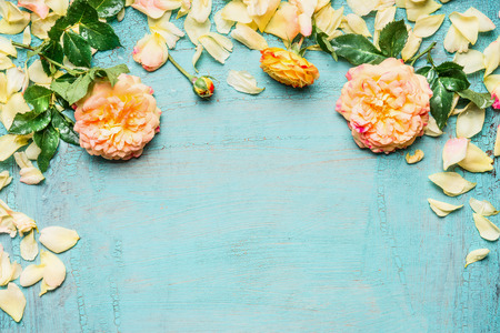 blue petals: Yellow pink roses with leaves and petals on light blue background, top view, floral border Stock Photo